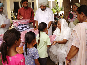 Mrs Surinder Kaur distributing school uniforms